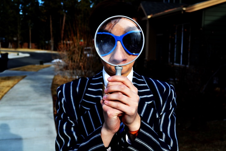 Man wearing blue sunglasses looks through a magnifying glass