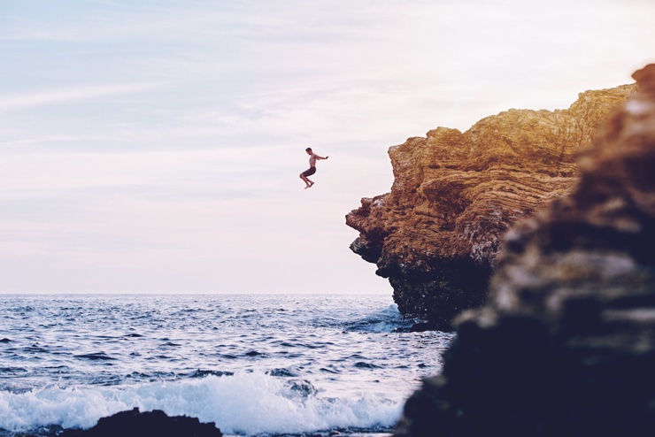 Man jumping off a cliff into the sea at sunset