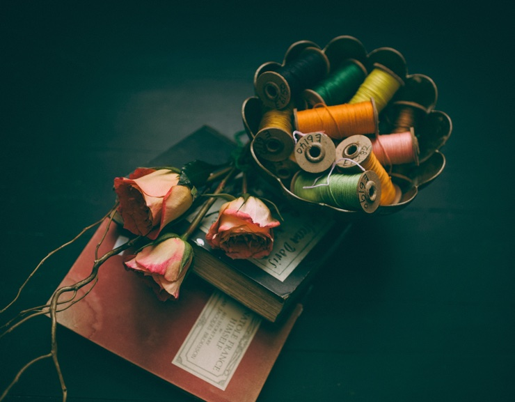 Roses, bobbins and books on a table