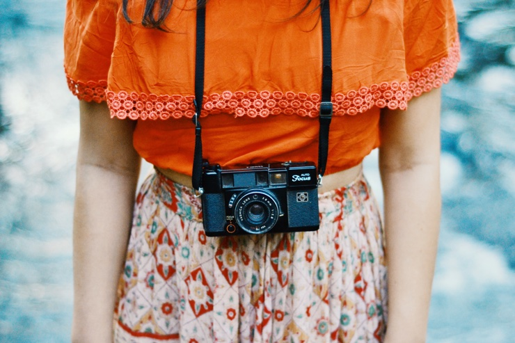 Woman in orange top with camera round her neck