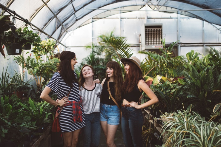 Four young women smile in a greenhouse