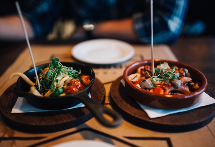 Two tapas dishes on wooden boards filled with delicious-looking fresh food