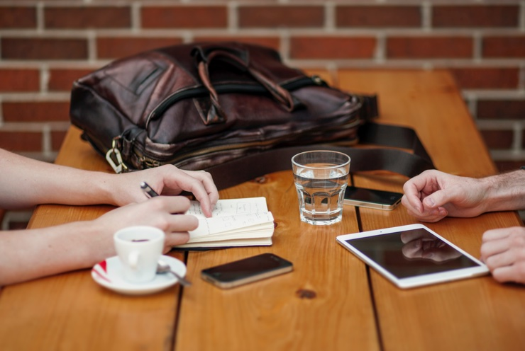 Two people sit at a table taking notes, with coffee and phones