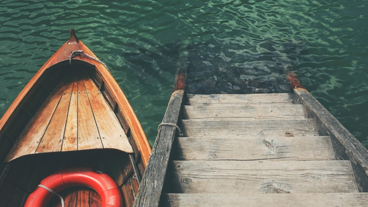 Wooden boat with a life ring floats beside a dock