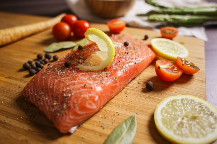 Colourful photograph of fresh salmon fillet with cherry tomatoes, lemon, seasoning and veg