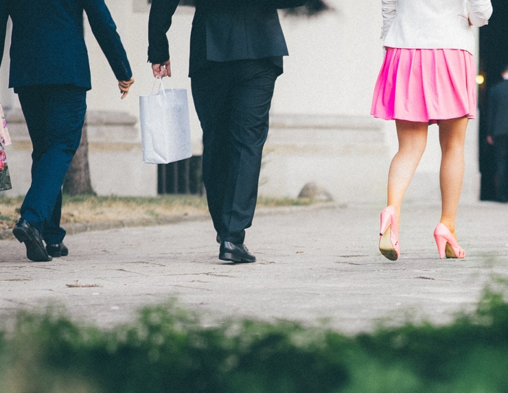 Smartly dressed men and woman walk down road