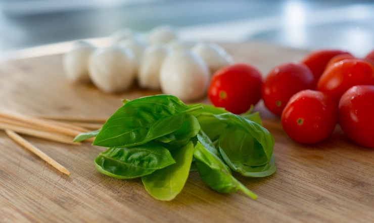 High res photo of food for a caprese salad - fresh basil, tomato and mozzarella