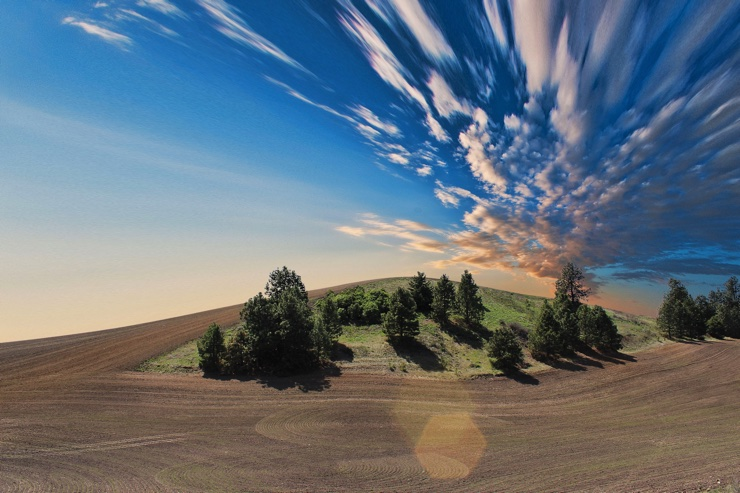 Clouds and blue sky over a ploughed field
