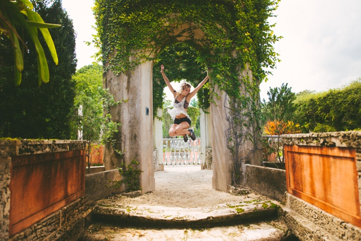 Excited young woman jumping for joy in beautiful sunny archway draped with vines