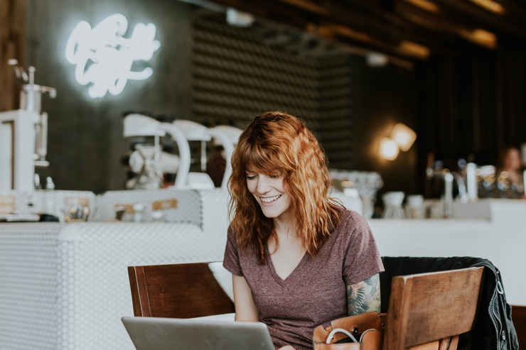 Woman with red hair smiles while looking at a laptop in a coffee shop