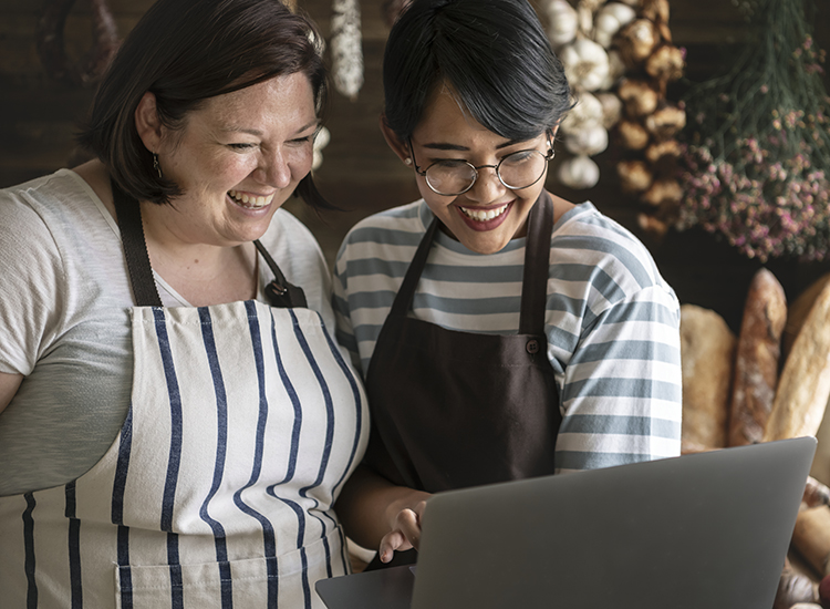 two ladies in a bakery smiling at a website