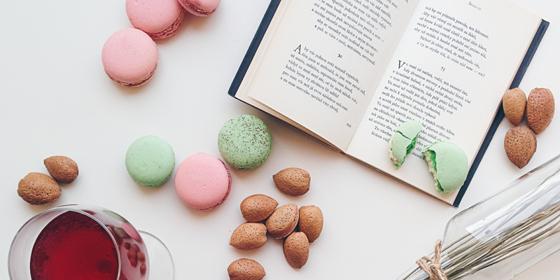 Picture of a book, macaroons and wine on a table