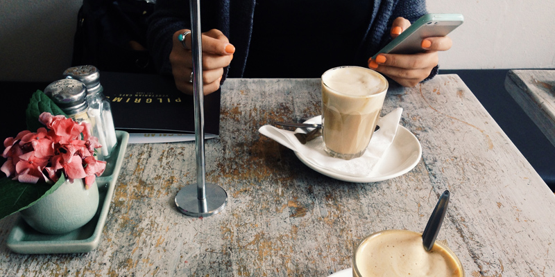 woman having a coffee while using her mobile