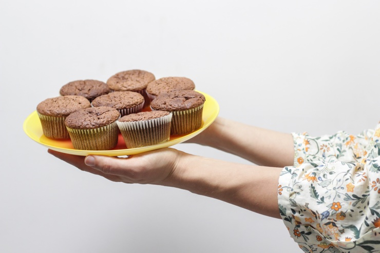Woman offering a plate of cupcakes