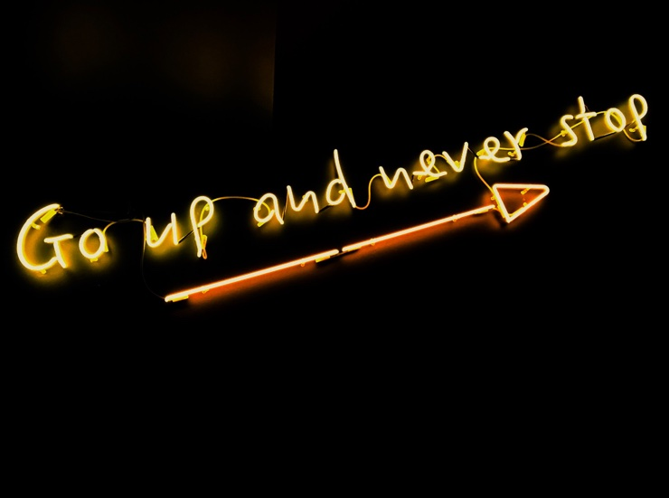 Neon sign reading 'Go Up and Never Stop'