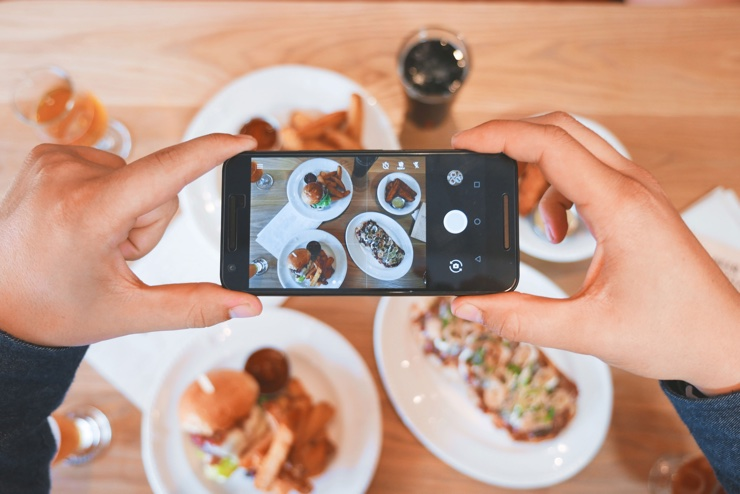 Woman taking a picture of her food from above on a mobile phone
