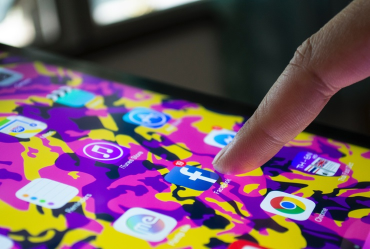Finger touching phone screen with social media icons