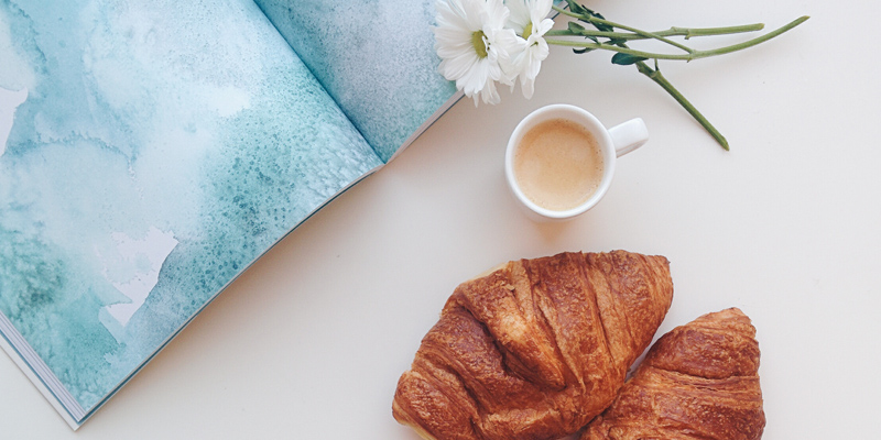 Stock image from Foodies Feed of a croissant, tea, flower and book