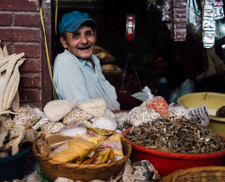 Happy man stands behind food stall at market