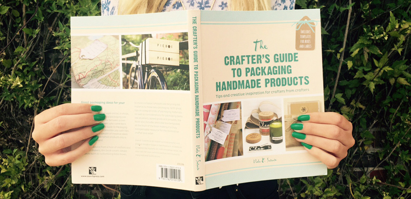 Image of woman holding the book The Crafter's Guide To Packaging Handmade Products