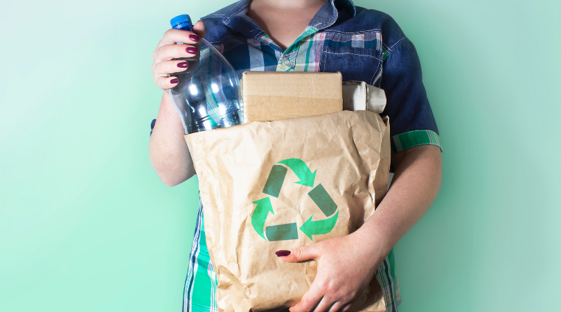 A person carrying a small bag of recycling