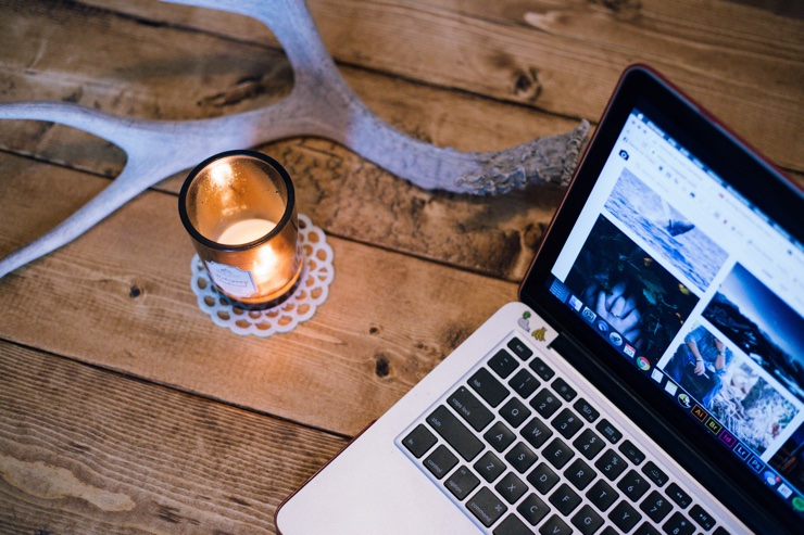 Pretty candle and laptop on rustic wooden table